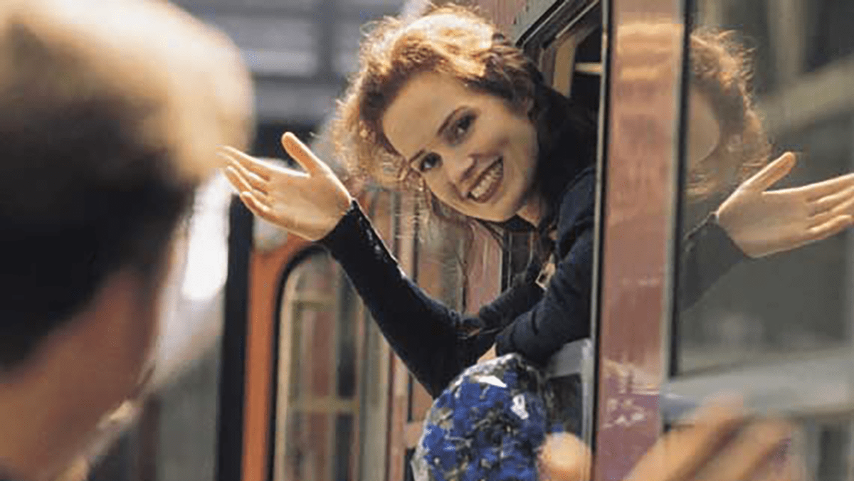 Daughter waving goodbye to parents out of train window