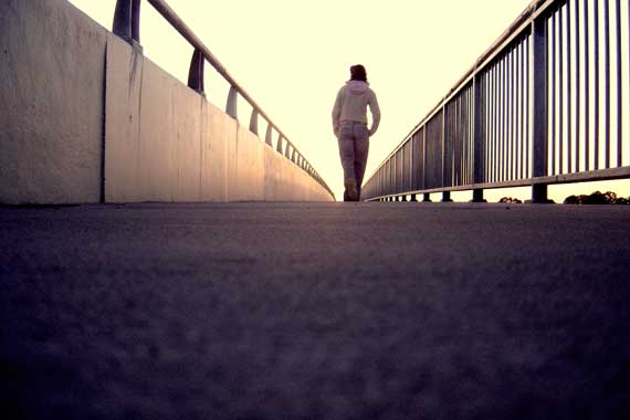 Woman walking alone on a bridge