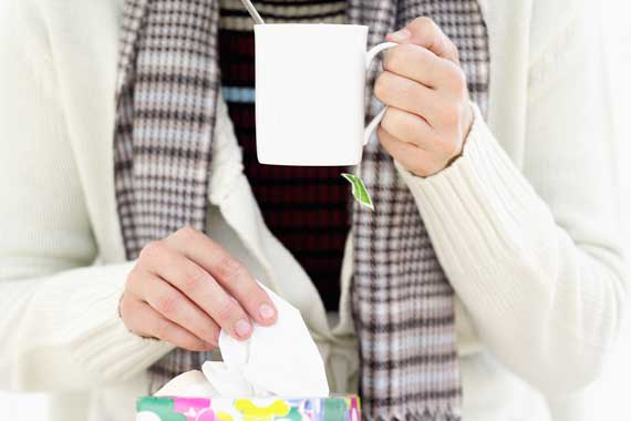 Woman with tissues and tea.