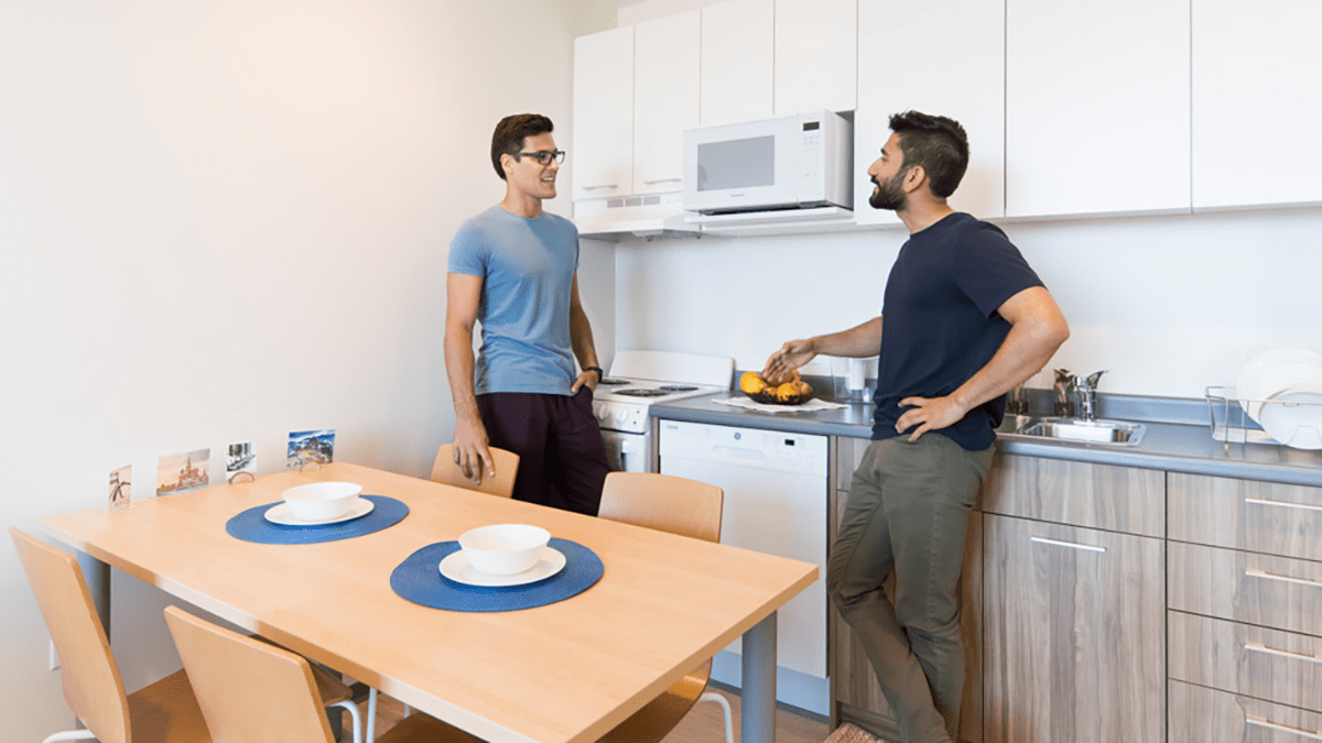 Two roommates talking in kitchen