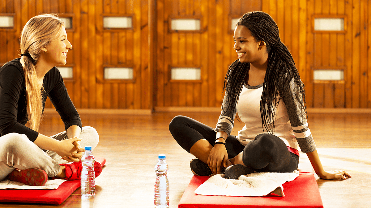 Two friends sitting on yoga mats and smiling