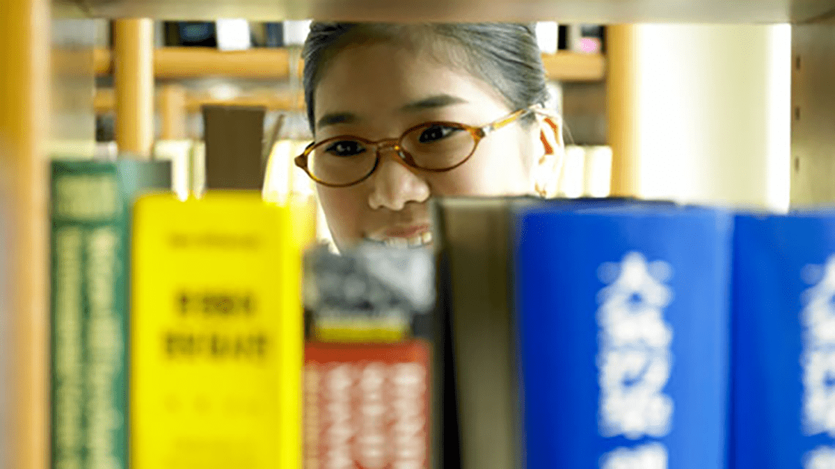 Student scanning books in a library