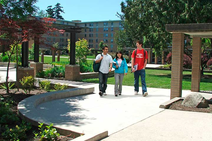 Students chat on a walkway between houses at Place Vanier, UBC.