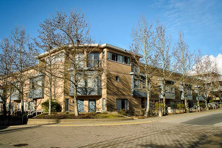 Exterior view of Thunderbird residence, located on a cobblestone street lined with trees at UBC.