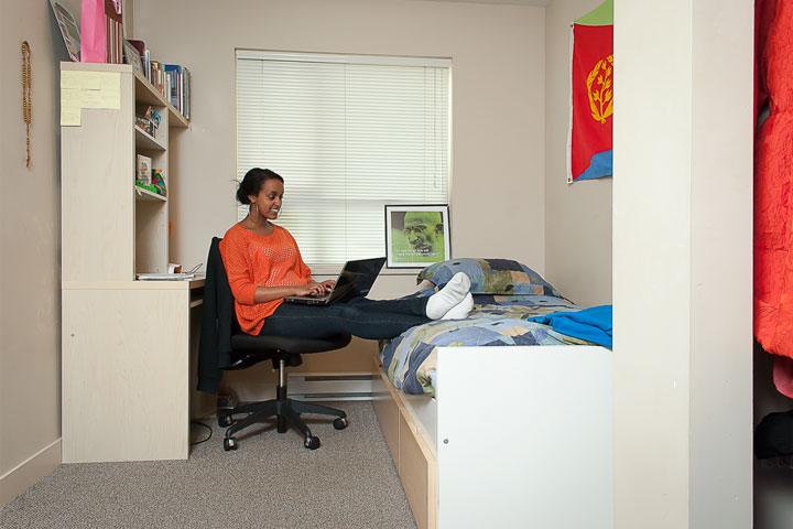 UBC Fraser Hall resident uses a laptop in her private bedroom.