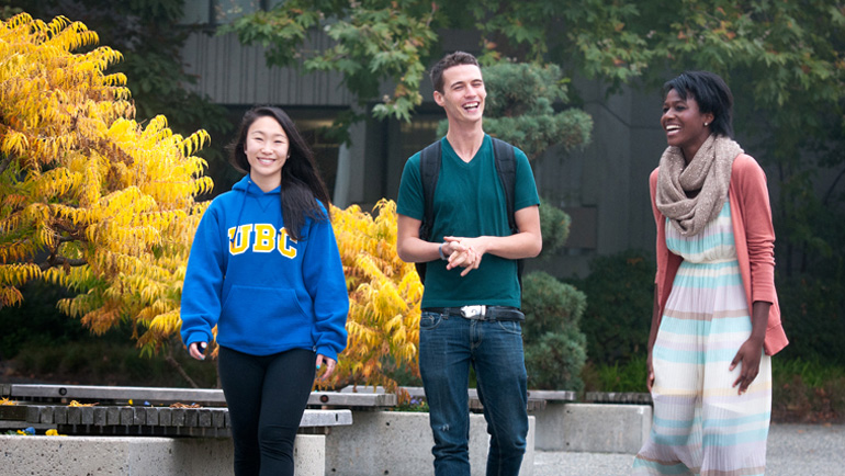 Three students walking on campus.