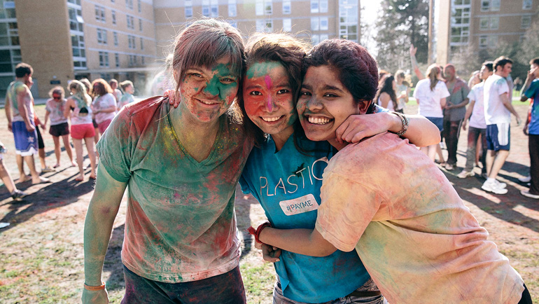 Three happy female students covered in paint.