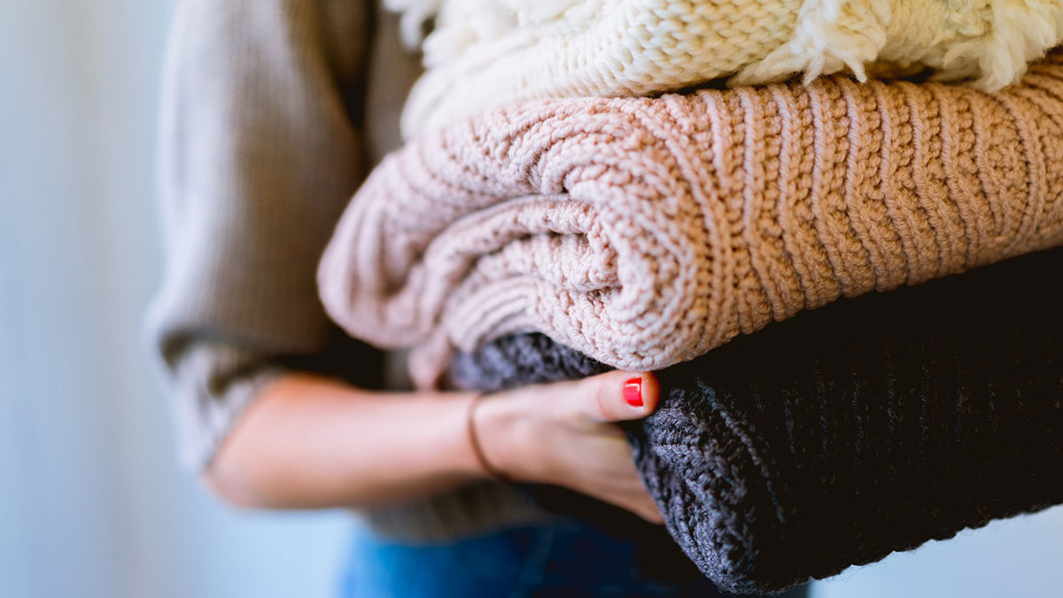Woman holding pile of knit blankets