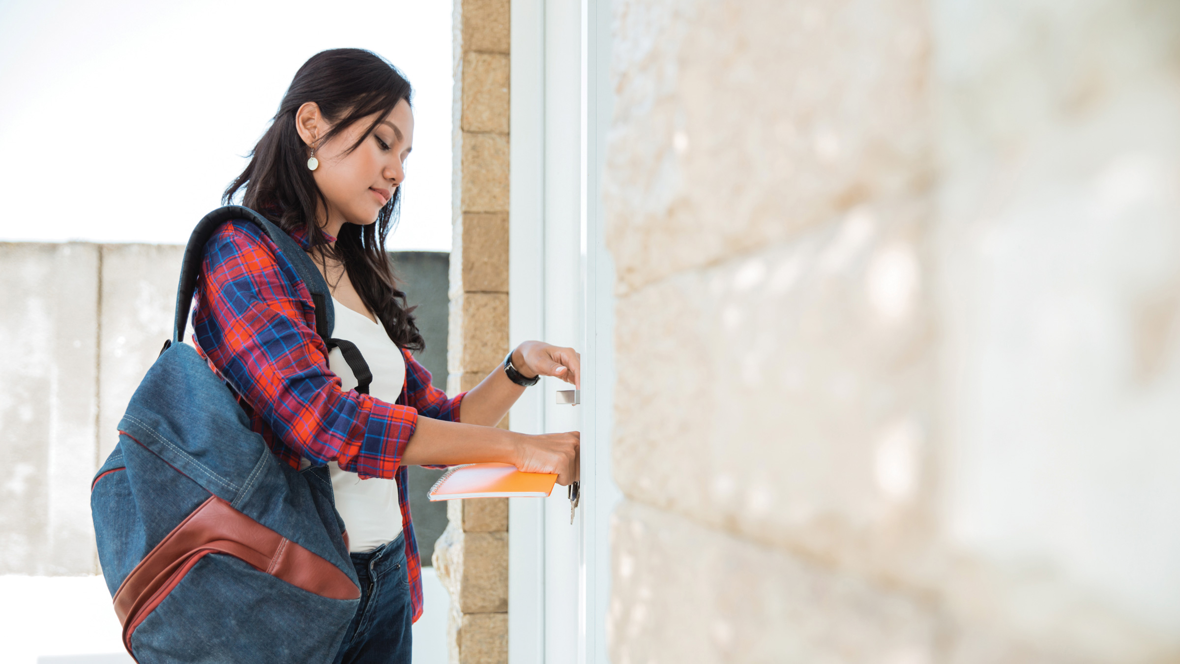 Young woman closing and locking her residence unit door