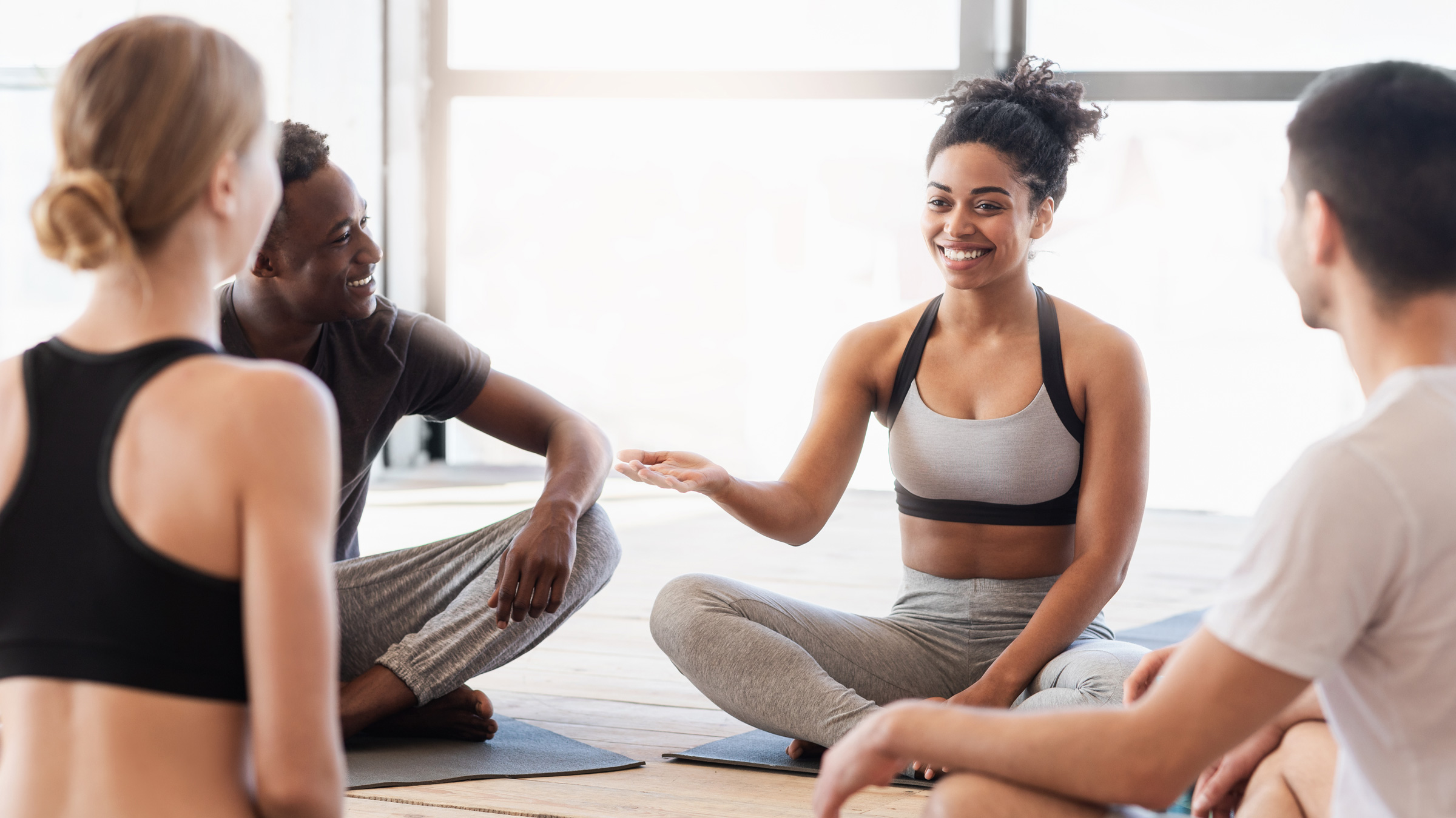 Black female yoga teacher speaking to her yoga students