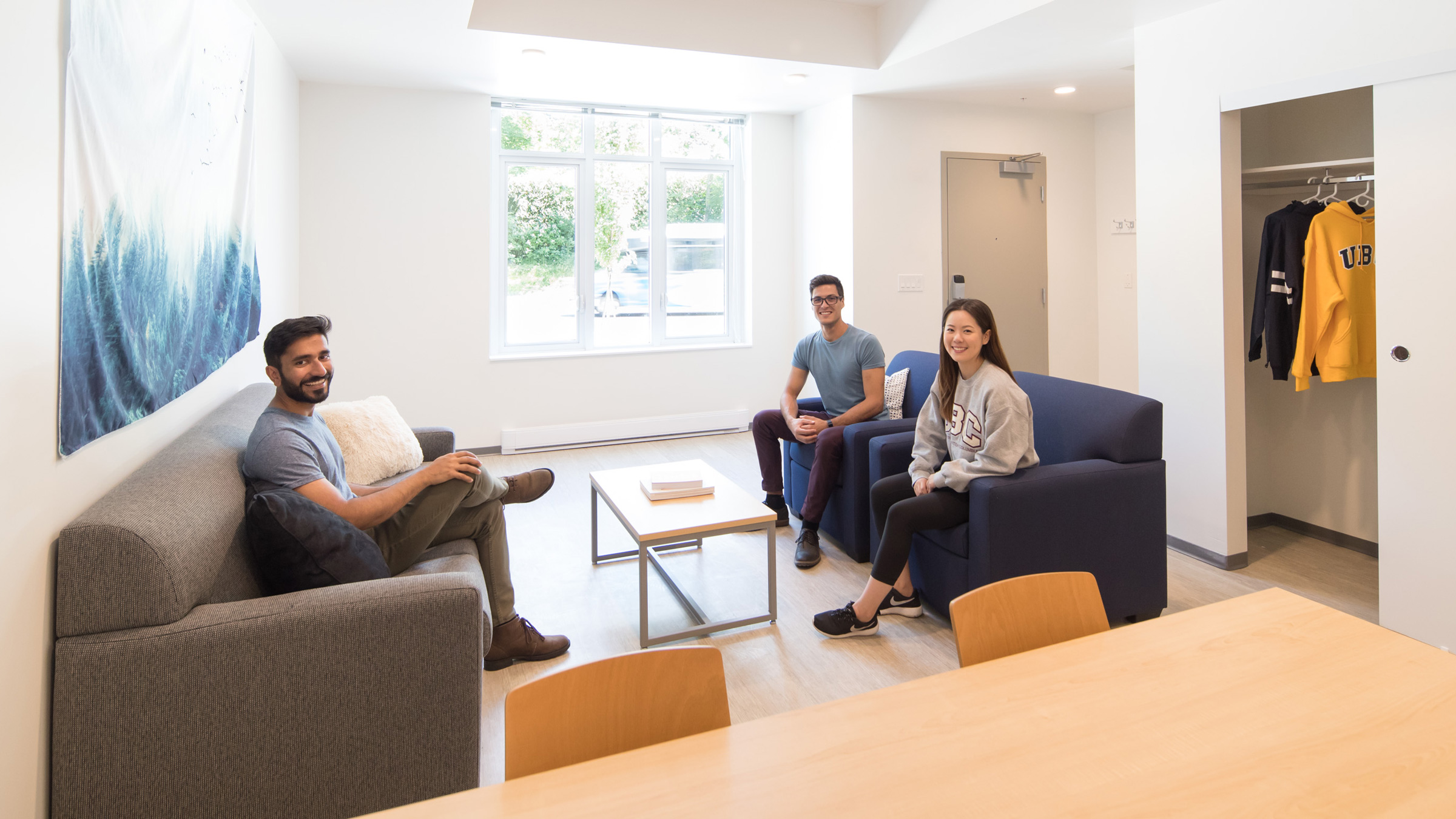 Three smiling students sit in the living room area of a residence room.